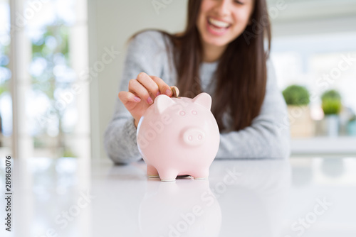 Fototapeta Young woman smiling putting a coin inside piggy bank as savings for investment obraz