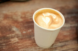 Beautiful cappuccino with a heart in a paper cup