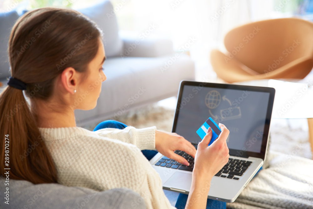 Fototapeta Woman shopping online with her credit card