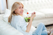 canvas print picture - Mature woman eating a healthy salad on her sofa