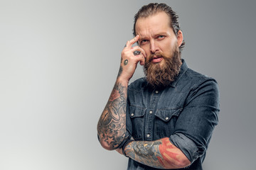 Tired tattooed man with beard is posing for photographer at photo studio.