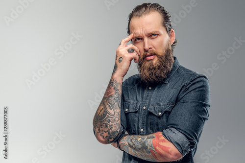 Tired tattooed man with beard is posing for photographer at photo studio Tablou Canvas