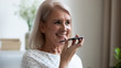canvas print picture Smiling mature woman recording voice message on phone close up