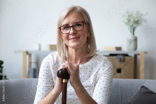 Head shot portrait beautiful older woman in glasses with cane