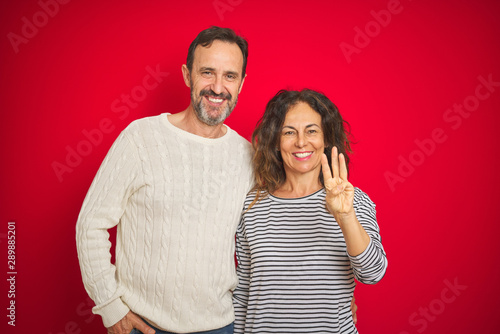 Photo  Beautiful middle age couple wearing winter sweater over isolated red background showing and pointing up with fingers number three while smiling confident and happy