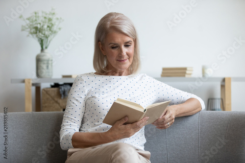 Fotografía  Beautiful mature woman reading book, sitting on couch at home