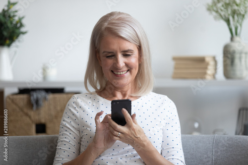 Smiling mature woman holding phone, using mobile device apps - 289886610