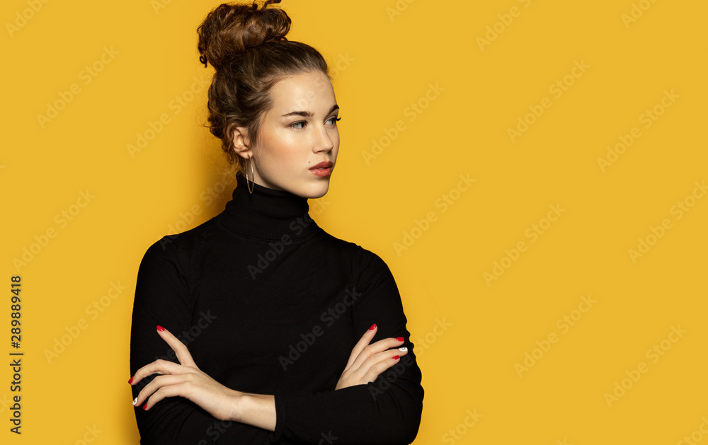 Fototapety, obrazy: Portrait of beautiful girl posing for fashion photoshoot on yellow background. Pretty model dressed in stylish black pullover. Trend and lifestyle concept