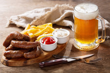 Fried Sausages With French Fries On Wooden Board And Mug Of Beer