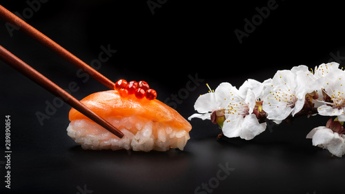 Fototapeta Sushi with red caviar and white flowers on a black table. Macro obraz
