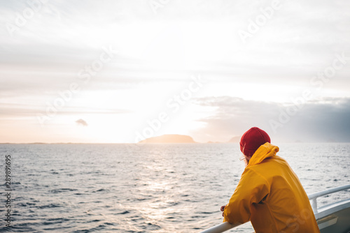 Fotomural  Young traveler wearing red hat and yellow raincoat floating on ship looking at sunset sea after storm and foggy mountains on skyline