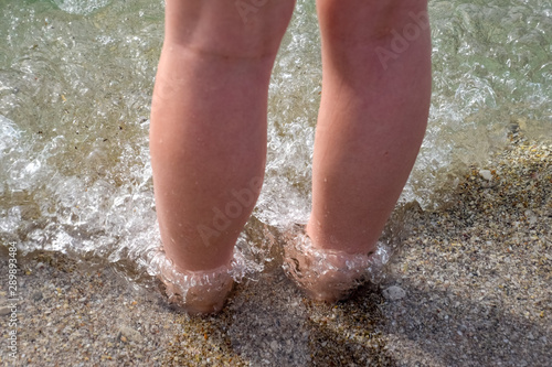 Photo Female legs ashore in sea water and sand.