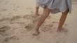 close up of foot walking on white soft sand on the beach