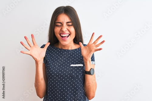 Fotografia  Young beautiful woman wearing blue casual t-shirt standing over isolated white background celebrating mad and crazy for success with arms raised and closed eyes screaming excited