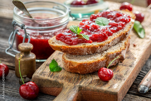Closeup of homemade sandwich with jam made of cherries - 289898421