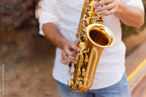 Fotografie, Obraz Close up of a man passionately playing the saxophone at the street