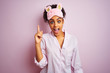 Young african american woman wearing pajama and mask over isolated pink background pointing finger up with successful idea. Exited and happy. Number one.