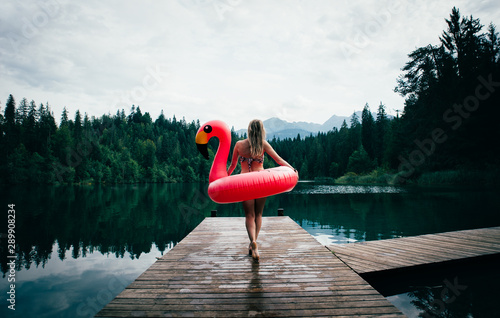 Fototapeta Woman having fun with flamingo at lakeside place