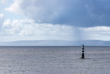 Lighthouse In Galway Bay With Rainy Cloud And Burren Mountains In Background