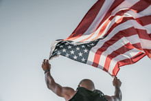 Low Angle View Of An Athlete Running On Athletic Track Holding The American Flag Over The Head