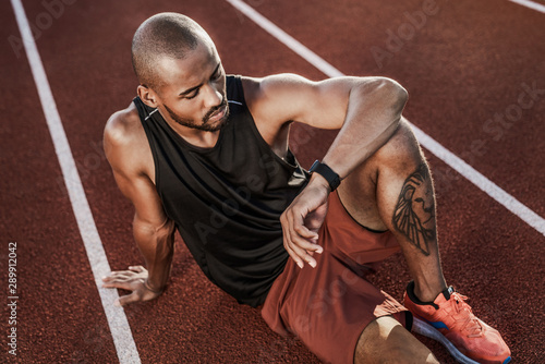 Valokuva  Young sportsman sitting on running track and looking at smartwatch