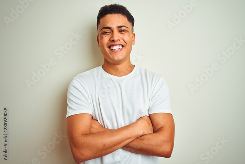 Foto Young brazilian man wearing t-shirt standing over isolated white background happy face smiling with crossed arms looking at the camera