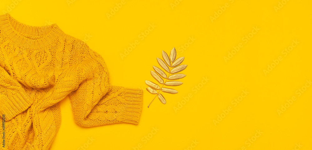 Fototapeta Autumn flat lay composition. Orange yellow knitted woolen female sweater and golden leaves on yellow background top view. Fashionable women's fall accessories. Cozy Knit Jumper Stylish Lady Clothes