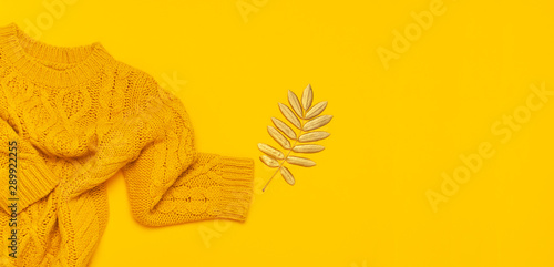 Aluminium Prints Equestrian Autumn flat lay composition. Orange yellow knitted woolen female sweater and golden leaves on yellow background top view. Fashionable women's fall accessories. Cozy Knit Jumper Stylish Lady Clothes