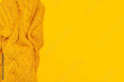 Autumn flat lay composition. Orange yellow knitted woolen female sweater on yellow background top view copy space. Fashionable women's fall winter accessories. Cozy Knit Jumper Stylish Lady Clothes