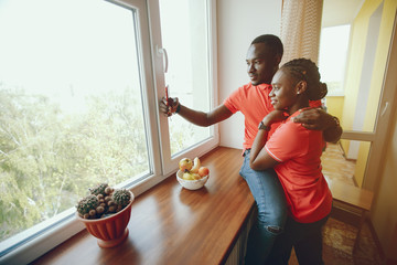a beautiful young black girl in a pink T-shirt and blue jeans standing at home near window with her boyfriend and use the phone