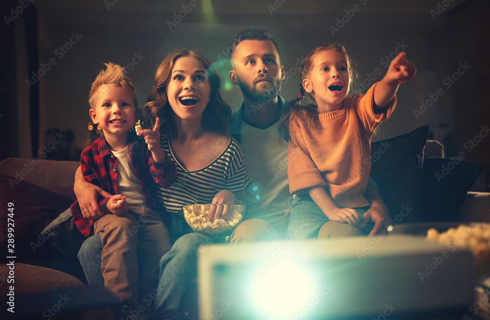 Fototapety, obrazy: family mother father and children watching projector, TV, movies with popcorn in   evening   at home.