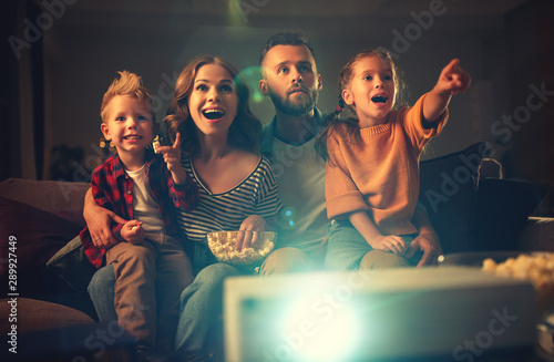 family mother father and children watching projector, TV, movies with popcorn in   evening   at home Fototapeta