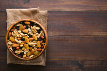 Healthy Trail Mix Snack Made Of Nuts (walnut, Almond, Peanut) And Dried Fruits (raisin, Sultana) In Wooden Bowl, Photographed Overhead With Copy Space On The Right Side