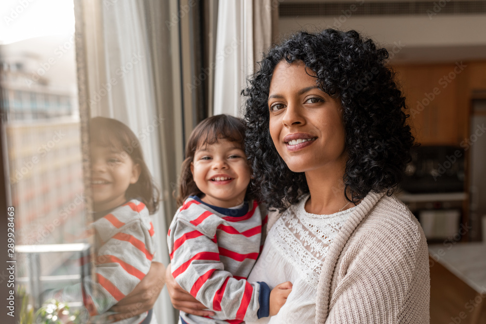 Fototapety, obrazy: Smiling mother and daughter standing by their living room window