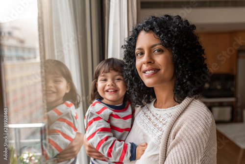 Fotografia  Smiling mother and daughter standing by their living room window
