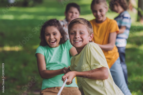 Carta da parati  selective focus of happy kids competing in tug of war