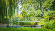 Metal Bridge Across A River In Green Garden / Park With Willow Or Sail Trees At Athelhampton (Admiston / Adminston) House, Settlement And Civil Parish In Dorset, England.