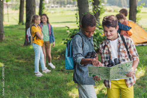 selective focus of african american kid looking at map near friend Wallpaper Mural