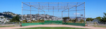Empty Baseball Infield With Backstop Against  Cityscape And Blue Sky.