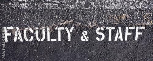 Fotomural  FACULTY & STAFF parking sign stenciled on parking lot asphalt.
