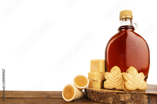 Fototapeta Maple syrup bottle and maple products on a wooden plank