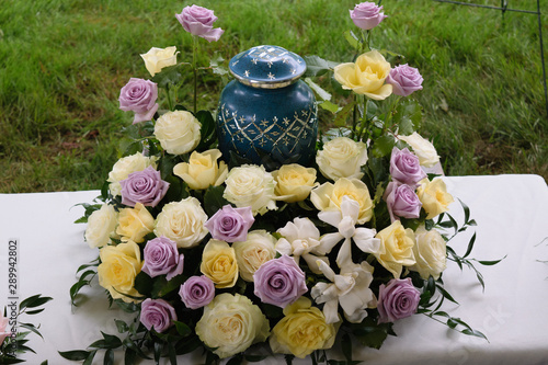 Foto funeral and mourning concept - flowers surrounding urn