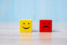 Smile Face On Yellow Wood Cube And Sad Face Icon On Red Wood Cube. Service Rating, Ranking, Customer Review, Satisfaction And Emotion Concept.