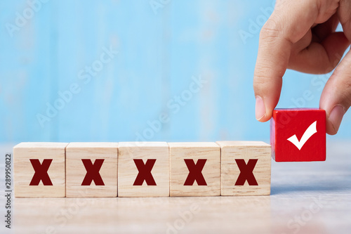 Photo  business man holding Wood cubes block with Right symbol different from Wrong sym