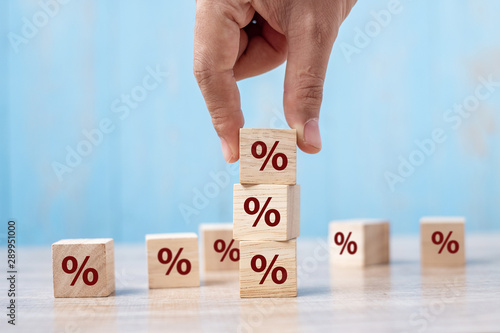 Fototapeta business man Hand putting wood cube block with percentage symbol icon. Interest rate,  financial, ranking and mortgage rates concept obraz