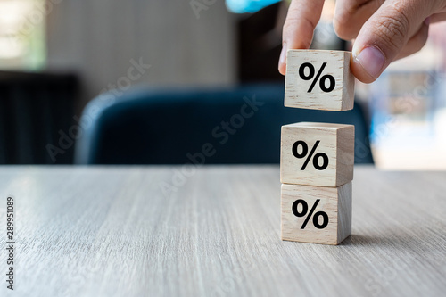 Obraz na plátně business man Hand putting wood cube block with percentage symbol icon