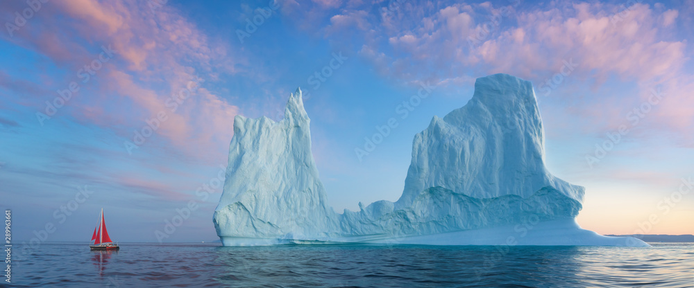 Fototapety, obrazy: Little red sailboat cruising among floating icebergs in Disko Bay glacier during midnight sun season of polar summer. Ilulissat, Greenland. Unesco world heritage