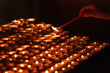 Hand Lighting Long Candle In Church. Rows Of Flames Of Candles In Traditional Religion Ceremony. Many Candle Flames In Darkness.