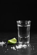 Vodka in shot glass on black background with a blank space for a text, Russian vodka with salt and lemon