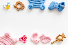 Blue And Pink Knitted Footwear, Hat, Dummy, Rattle Frame For Baby On White Background Top View Mockup